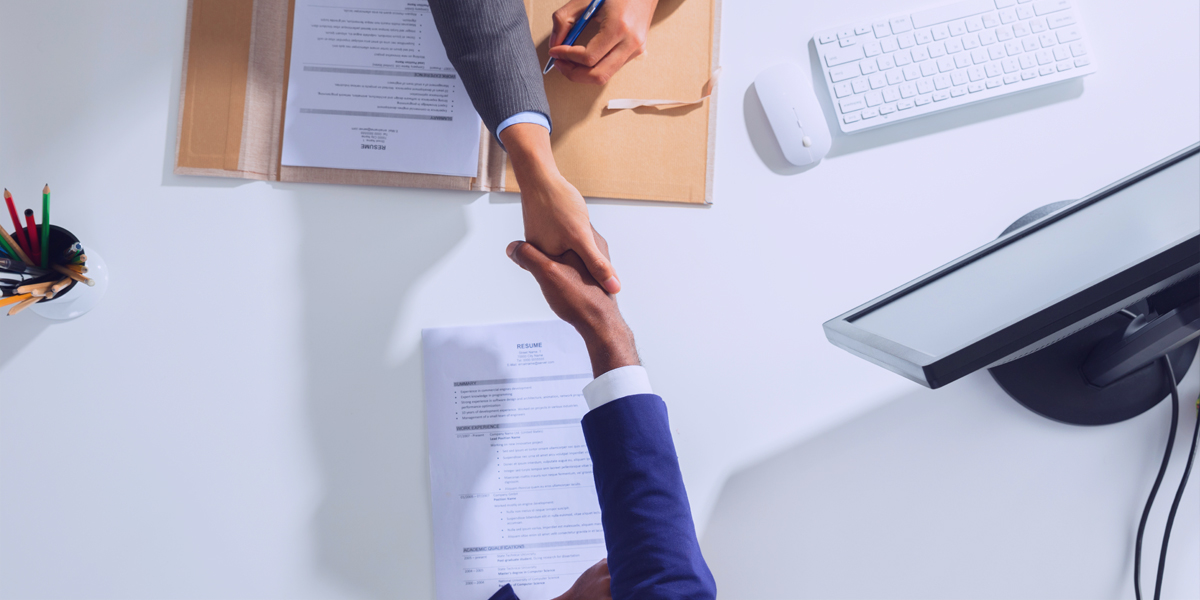 Two people shaking hands in an office over a table with computer and paper files