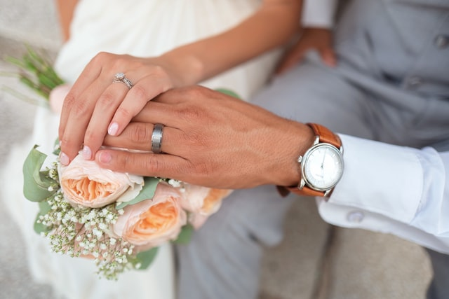 Bride and groom's hand on top of each other over a bouquet or roses
