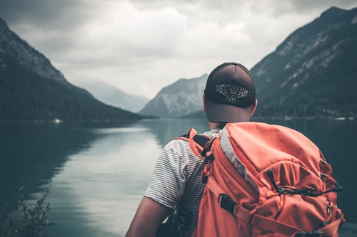 Man with backpack in hilly area