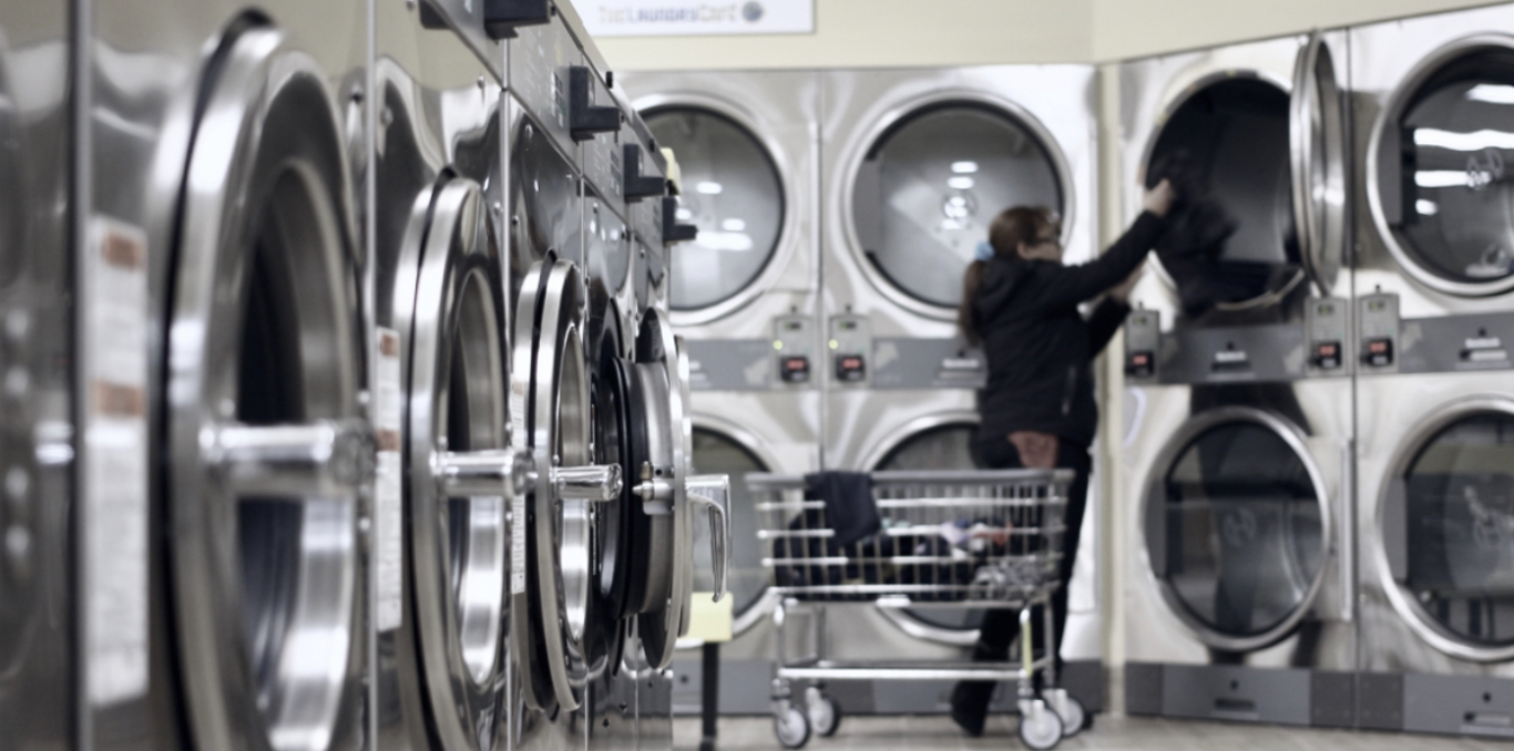 A women using a laundry store in a room full of laundry machines